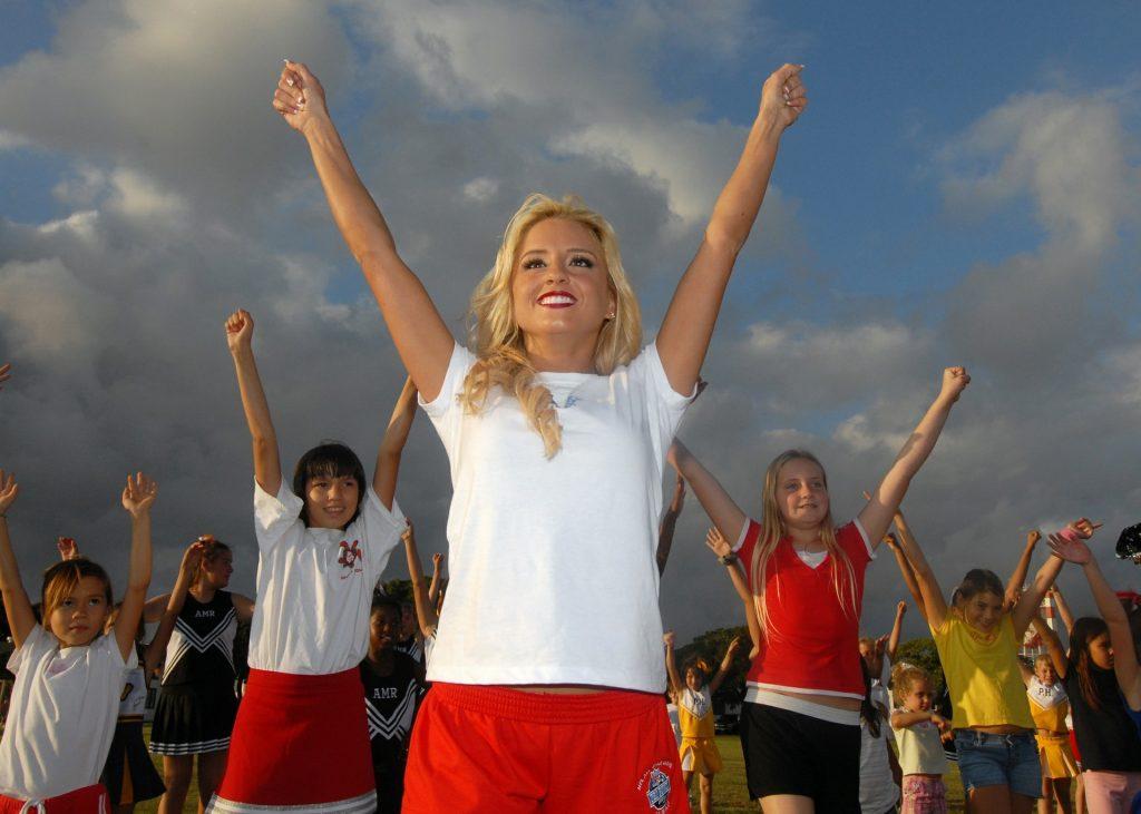 Gruppe von Mädchen reißen siegreich die Hände hoch
