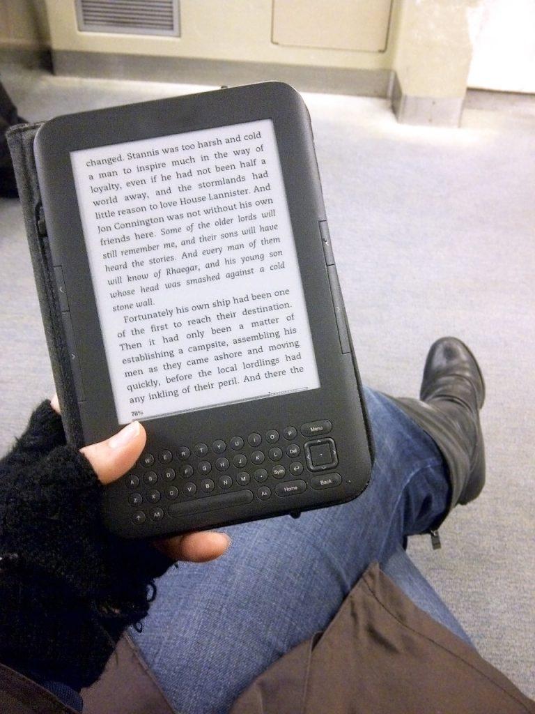 E-Book-Reader auf dem Schoß einer Frau in der Bahn