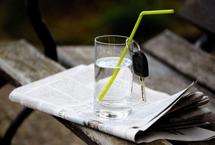 Wasserglas mit Strohhalm, an dem Autoschlüssel hängt
