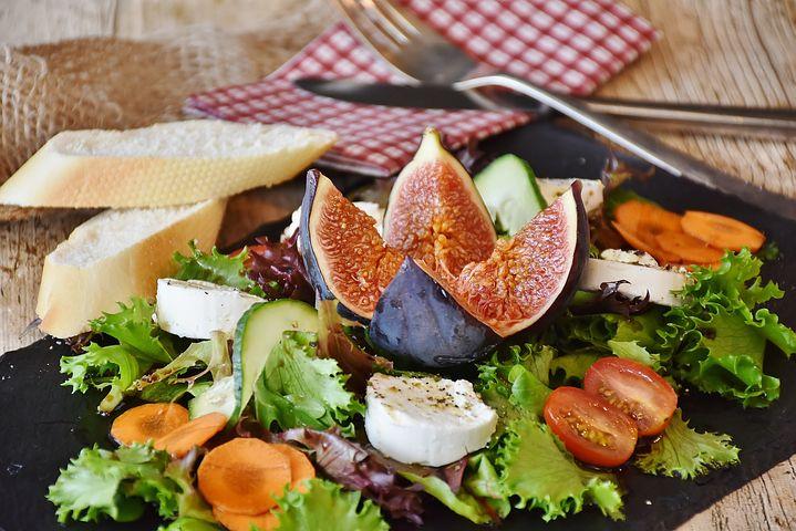 Schön angerichteter Salat mit Käse, Feige und Baguette