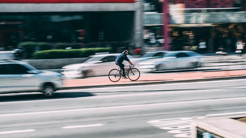 Radfahrer, im Hintergrund schnelle Autos