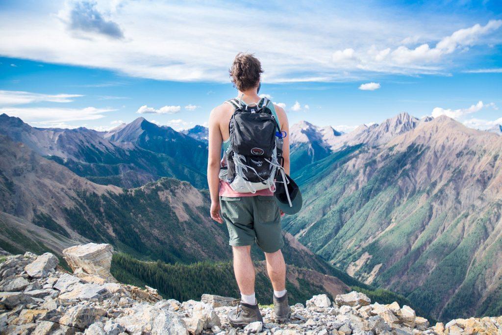 Wanderer mit Rucksack, der an einer Stelle mit schöner Aussicht in den Bergen steht und von hinten zu sehen ist.
