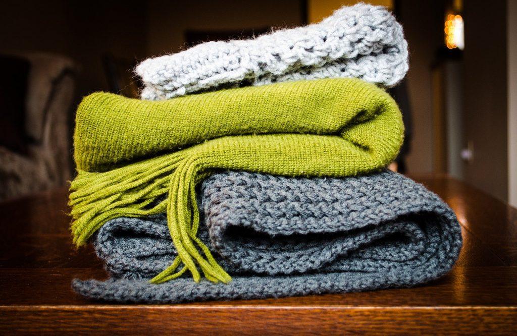 Ein Stapel mit Strickschals in drei verschiedenen Farben
