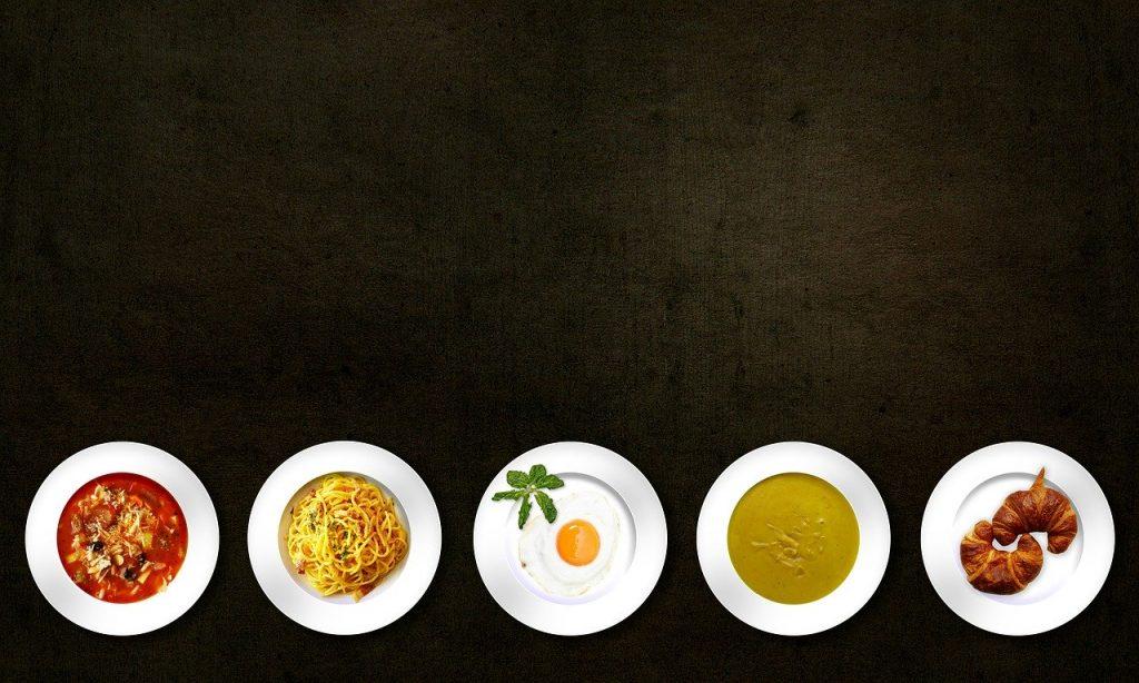 Fünf Teller vor dunklem Hintergrund von oben fotografiert, darauf eine Gemüse-Suppe, ein Spaghettigericht, ein Spiegelei, eine cremige grüne Suppe und zwei Croissants