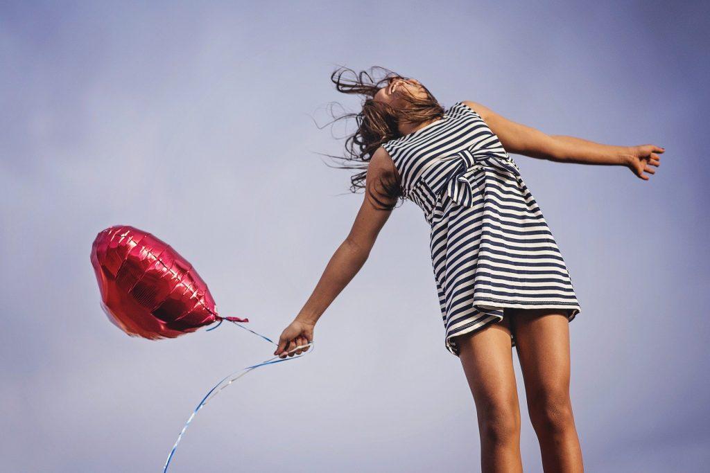 Frau mit Streifenkleid und Luftballon in der Hand, die in die Luft springt