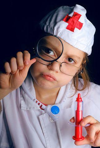 Mädchen im Sanitäter-Kostüm schaut durch Lupe
