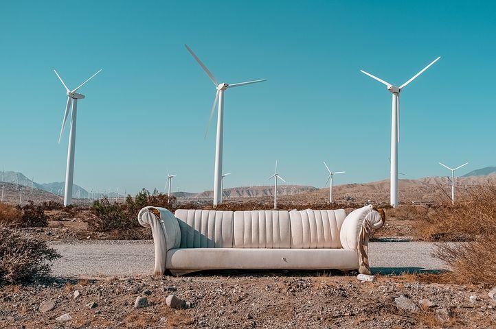 Altes Sofa in wüstenähnlicher Gegend vor Windrädern