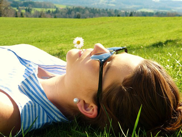 Frau entspannt im Gras liegend mit Sonnenbrille