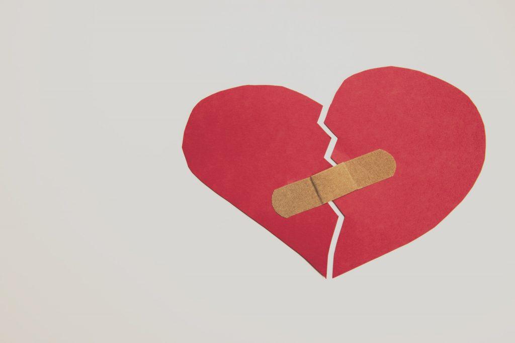 zwei Hälften eines Herz. Verbunden durch ein Pflaster.