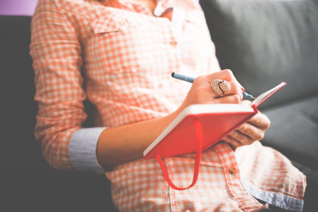 Eine Frau, die in ein rotes Tagebuch etwas einträgt