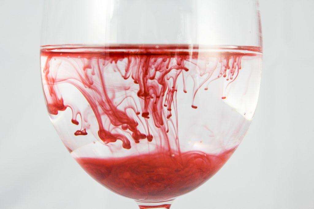 Weinglas mit Wasser, in dem rote Farbe verläuft.