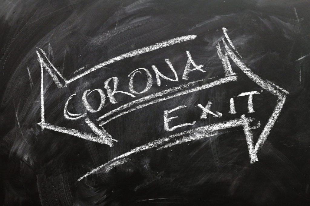 zwei weiße Kreidepfeile auf schwarzer Tafel auf denen Corona Exit steht