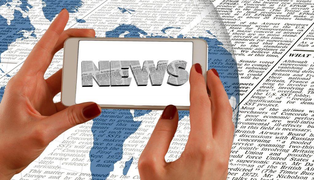 Zeitung, zwei Hände halten einen Smartphone, auf dem NEWS steht
