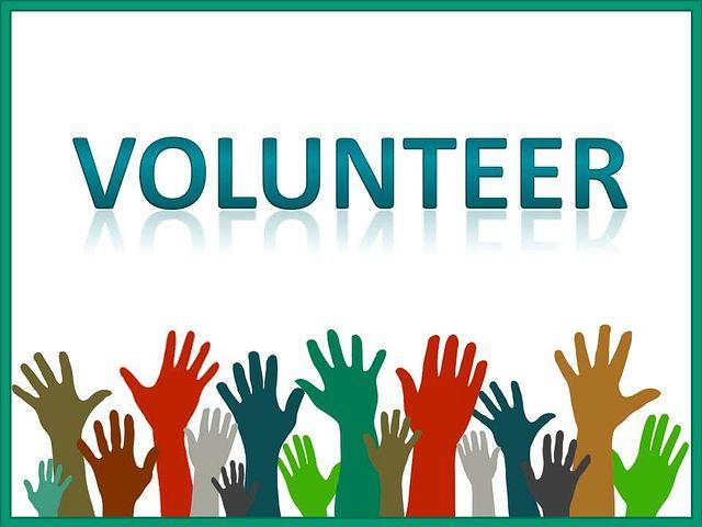 """Bunte Hände recken sich in die Höhe, Text """"Volunteer"""""""