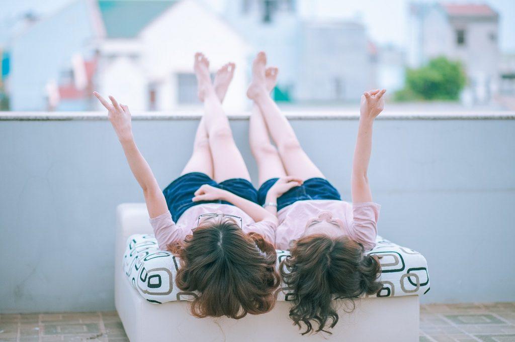 zwei Teenager-Mädchen, die nebeneinander auf einer Liege liegen und sich scheinbar unterhalten.