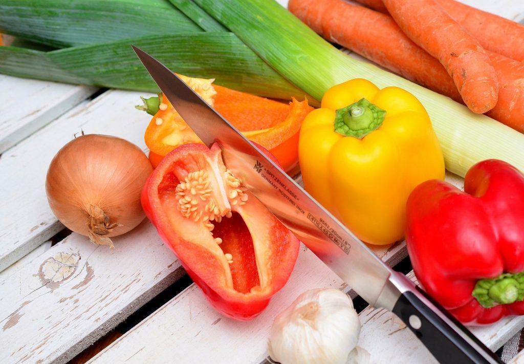 Gemüse wie Tomate, Paprika, Lauch und Zwiebel auf einem Schneidebrett