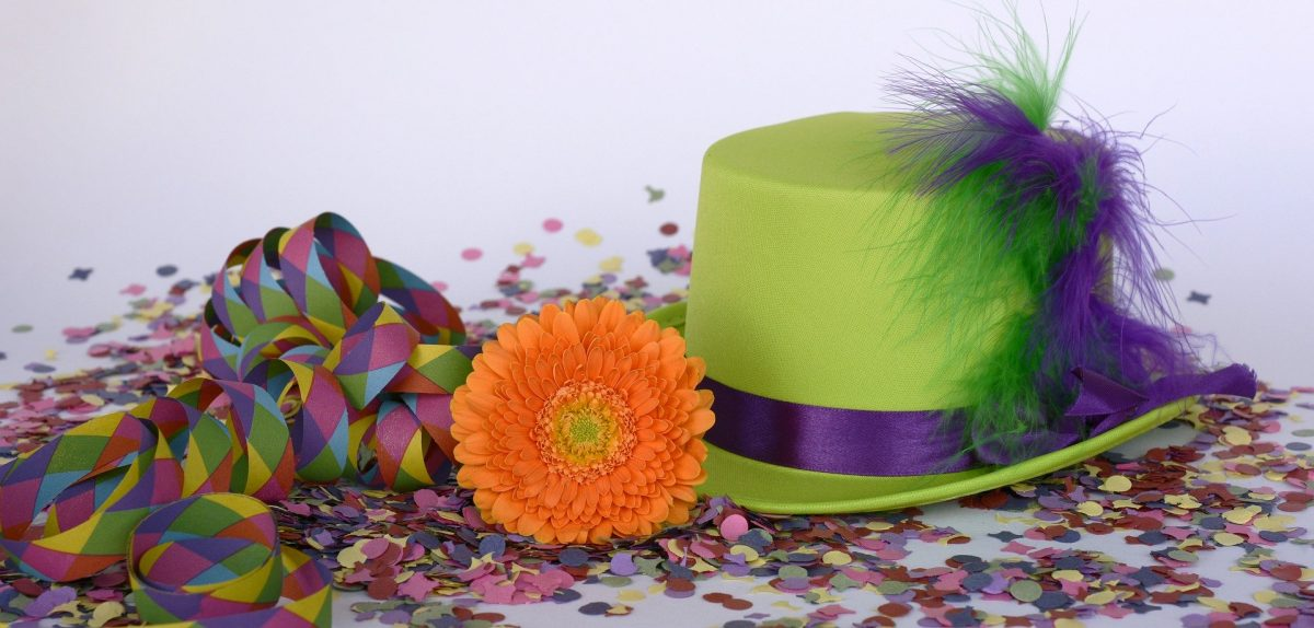 Grüner Hut mit Konfetti, Luftschlangen und Blume