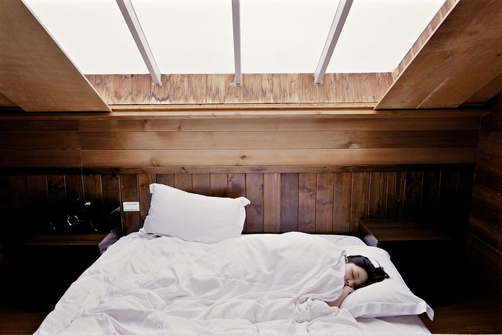 Schlafende Frau in einem Bett unter schrägem Dachfenster