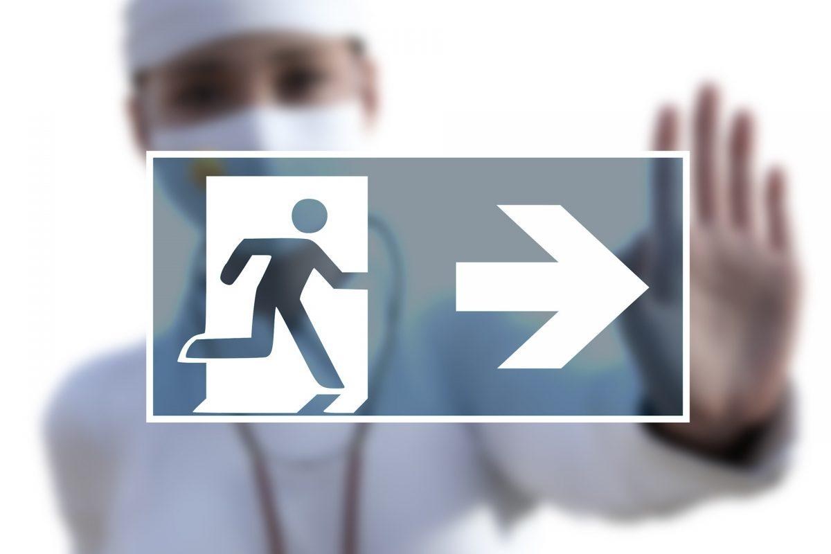 Piktogramm für Notausgang, im Hintergrund Mensch mit medizinischer Schutzkleidung, der mit der Hand ein Stop signalisiert
