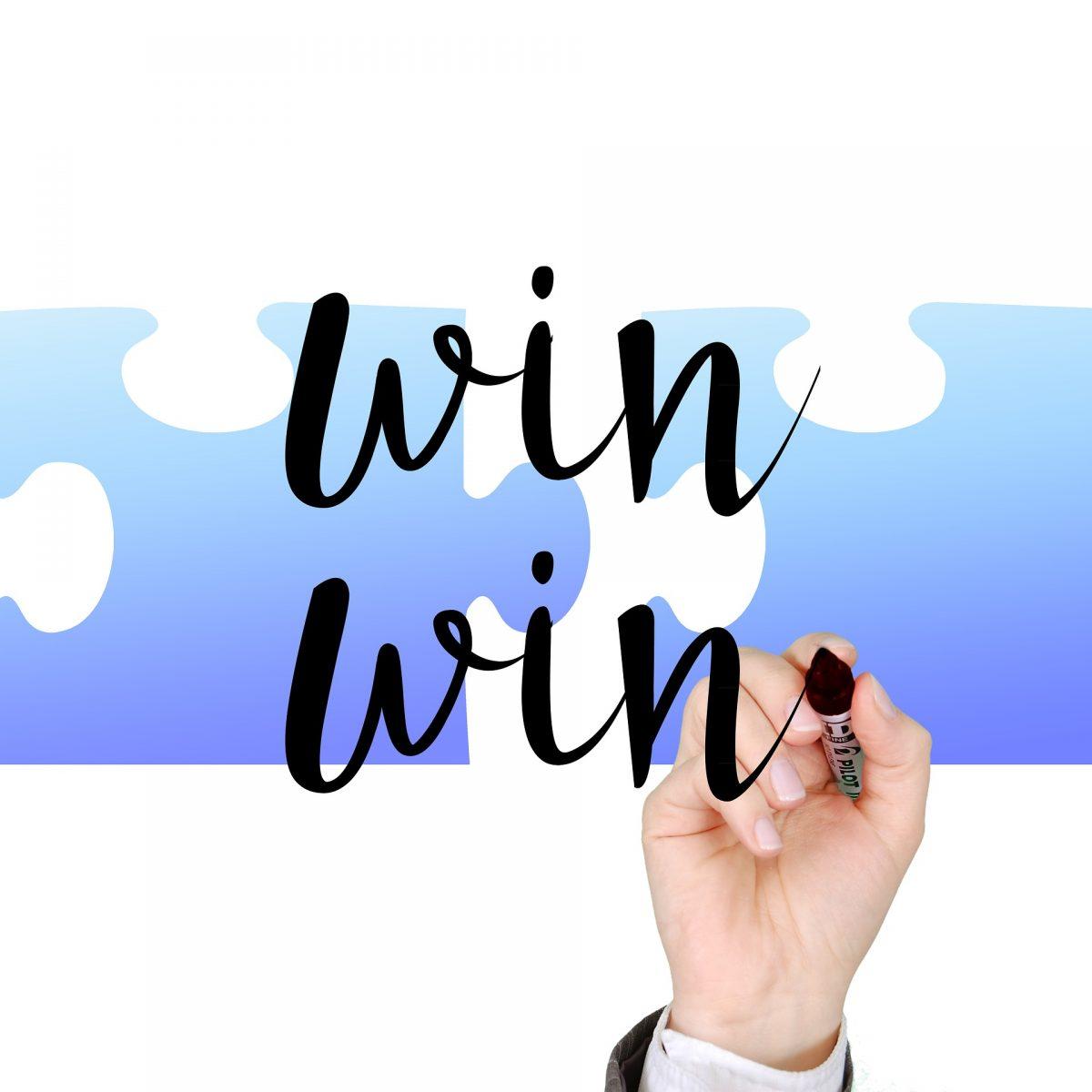 """Hand schreibt """"win win"""". Im Hintergrund, zwei blaue Puzzleteile"""