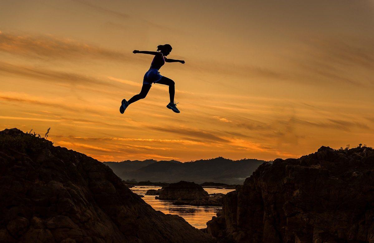 Frau springt über einen Abgrund, im Hintergrund das Meer und ein Abendhimmel