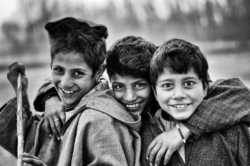 Das Bild ist in Schwarz Weiß und zeigt drei Jungs. Der Mittlere umarmt die beiden Anderen. Alle Drei sehen fröhlich aus.