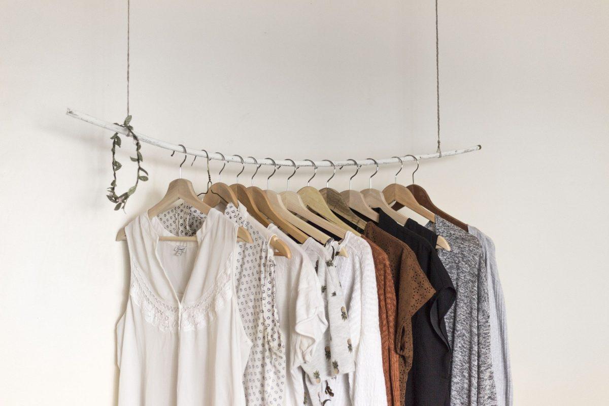 Kleiderstange mit farblich sortierten aufgereihten Kleidungsstücken