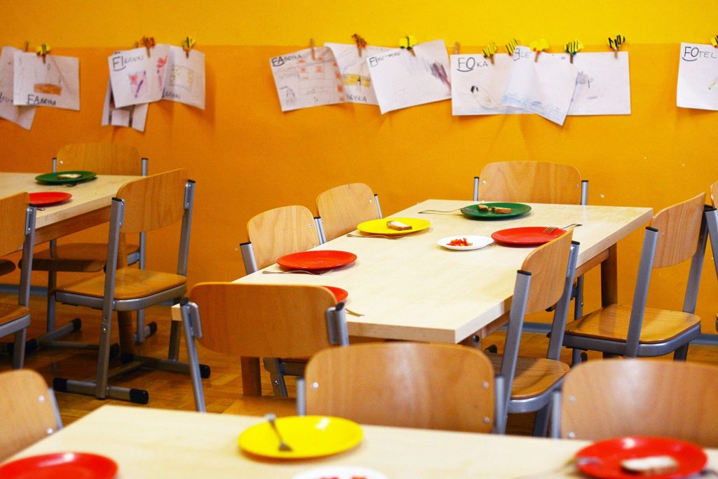 Kindergartenraum, Tische mit Stühlen und Bilder an der Wand