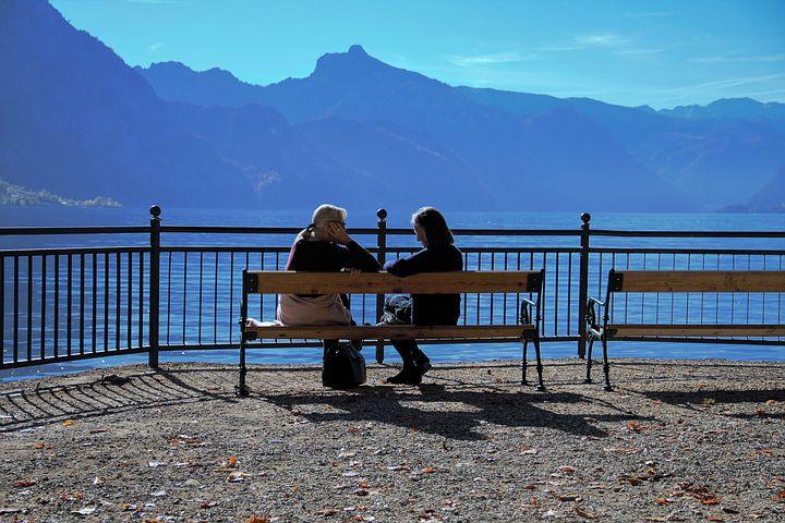 Zwei Frauen im Gespräch auf einer Bank am See