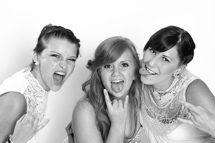 Drei Frauen schreien in die Kamera bzw. Strecken die Zunge raus und zeigen dabei den Rock'n'Roll-Gruß mit einer Hand
