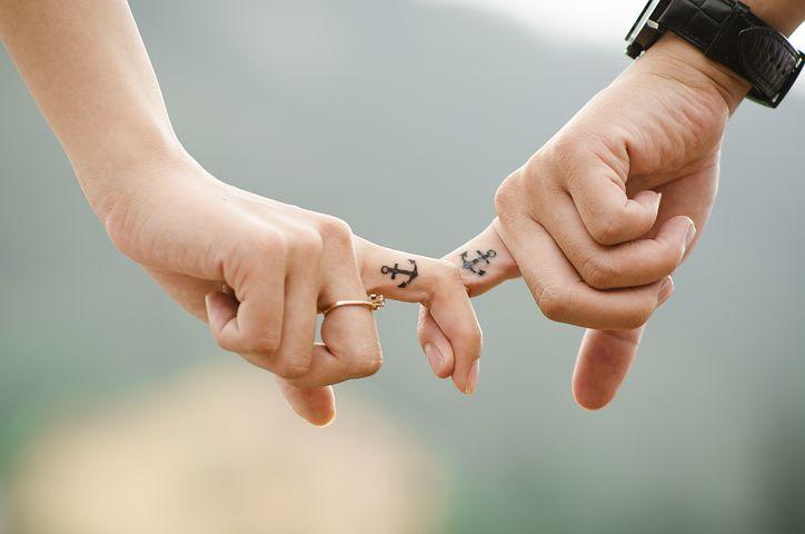 Eingehakte Zeigefinger eines Mannes und einer Frau, auf beiden Fingern ist ein Ankertattoo zu sehen.