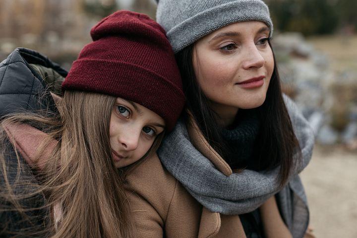 Zwei Frauen mit Mütze lehnen sich aneinander an