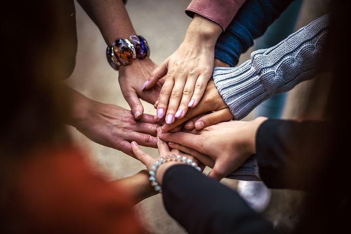 Hände von mehreren Personen liegen aufeinander im Kreis