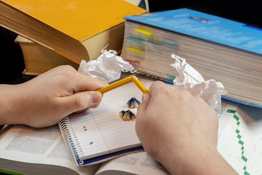 Hände zerbrechen Bleistift, Bücher und Zettel im Hintergrund