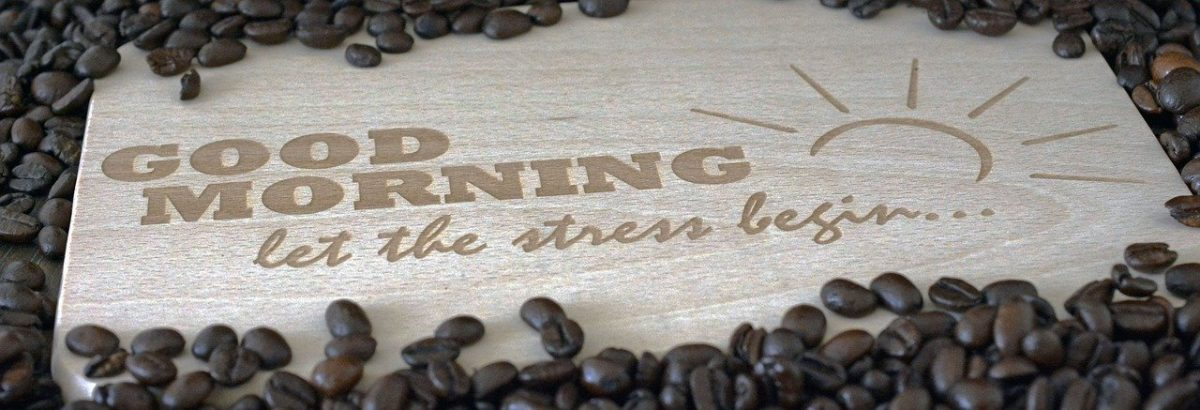 "Holzschild mit ""Good Morning let the stress begin""-Schriftzug, drumherum Kaffeebohnen"