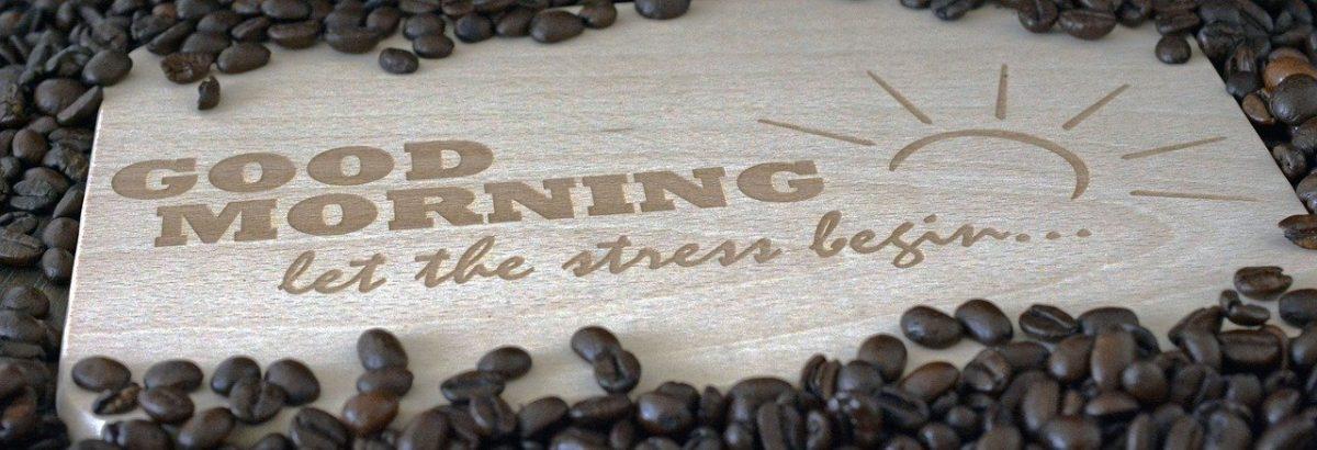 """Holzschild mit """"Good Morning let the stress begin""""-Schriftzug, drumherum Kaffeebohnen"""
