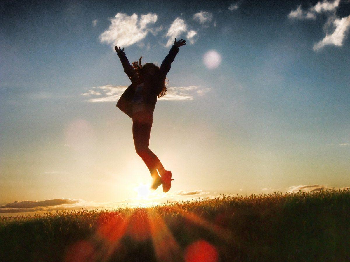 In die Luft springende Frau vor Sonnenuntergang