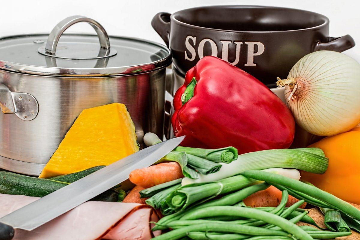 Topf und Suppenschale, davor ein goßes Messer und viel Gemüse zum Kochen