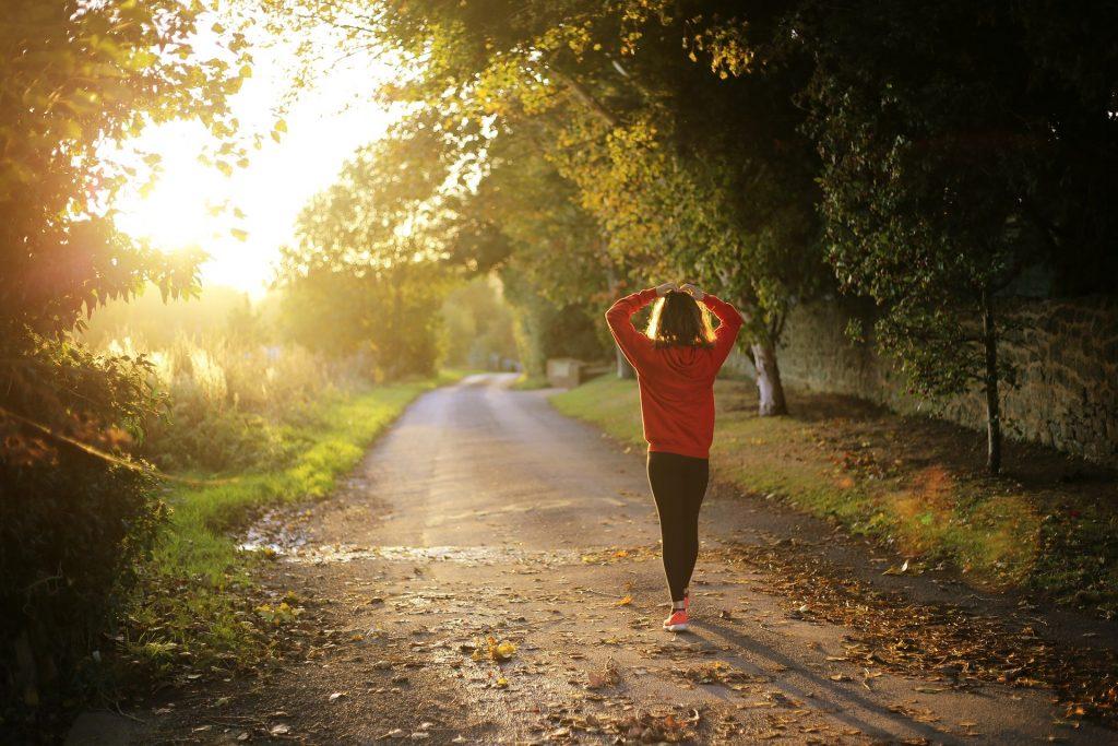 Frau wandert durch Wald, im Hintergrund Sonnenlicht