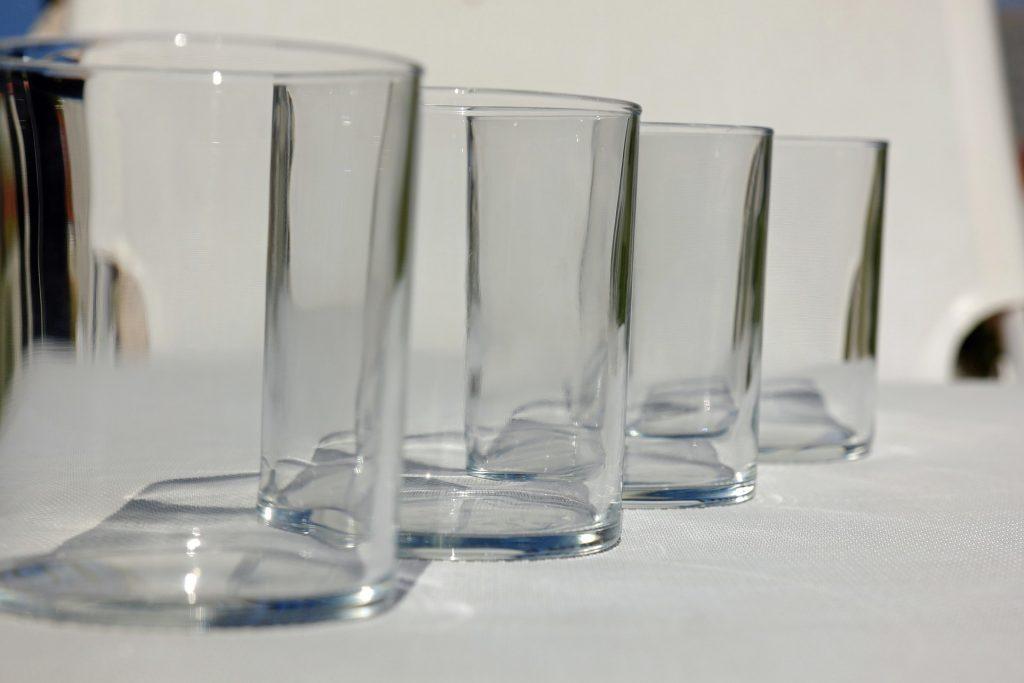 vier leere Wassergläser schräg hintereinander