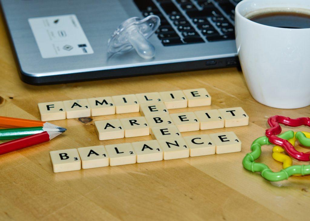 Scrabble-Buchstaben: Familie, Arbeit, Balance, Leben, im Hintergrund Notebook und Schnuller