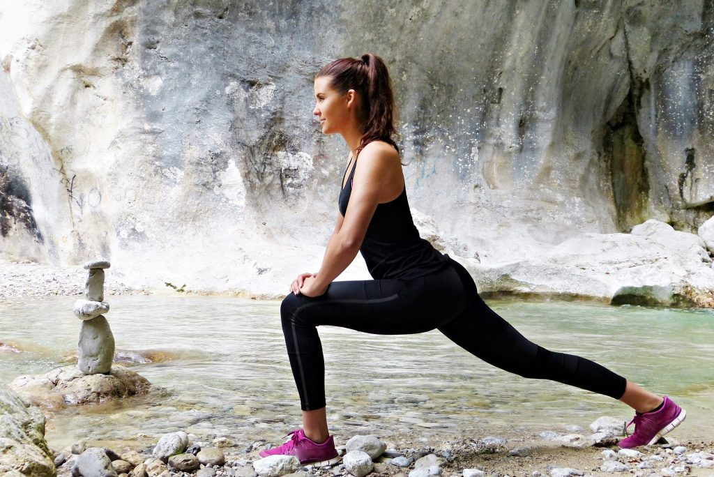 Frau dehnt sich am Fluß, im Hintergrund Wasserfall