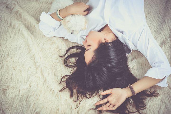 Schlafende Frau in bequemer Haltung mit Stofftier im Arm