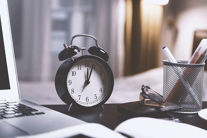 Wecker auf einem Schreibtisch mit Stiften, Laptop und Buch