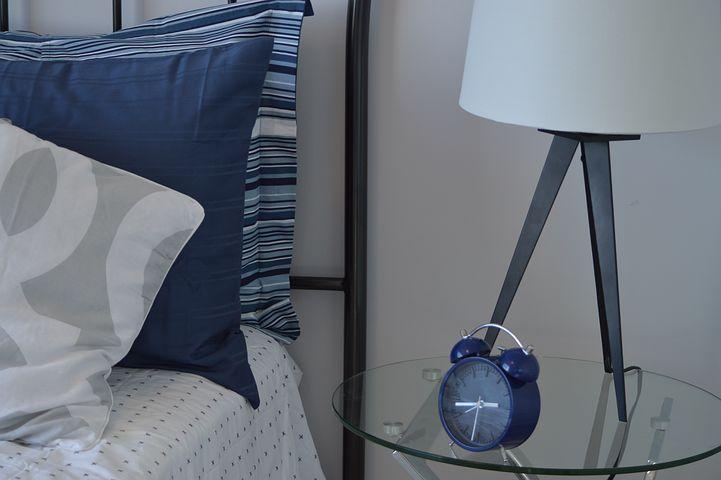 Nachttisch mit blauem Wecker und Nachttischlampe, daneben ist der Rand eines Bettes mit blauen Kissen zu sehen.