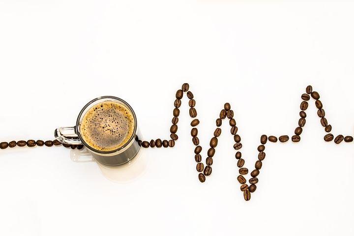 Tasse Kaffee und eine EKG-Linie aus Kaffeebohnen