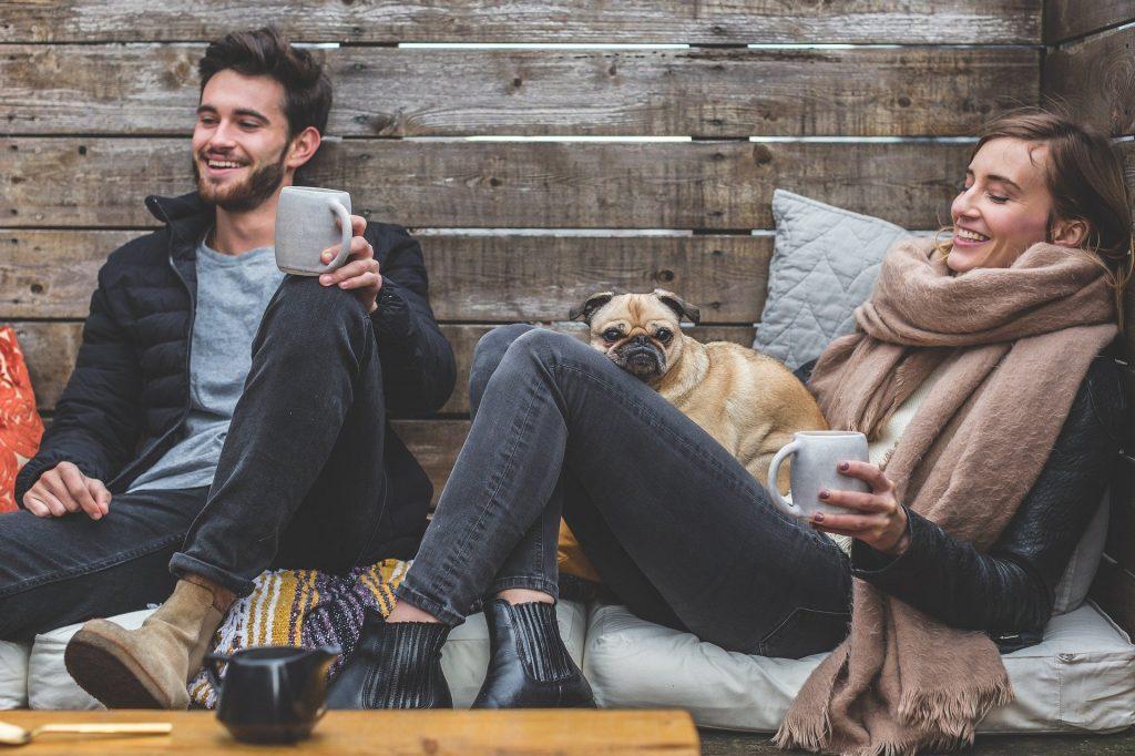 Paar sitzt entspannt draußen ud trinkt Tee