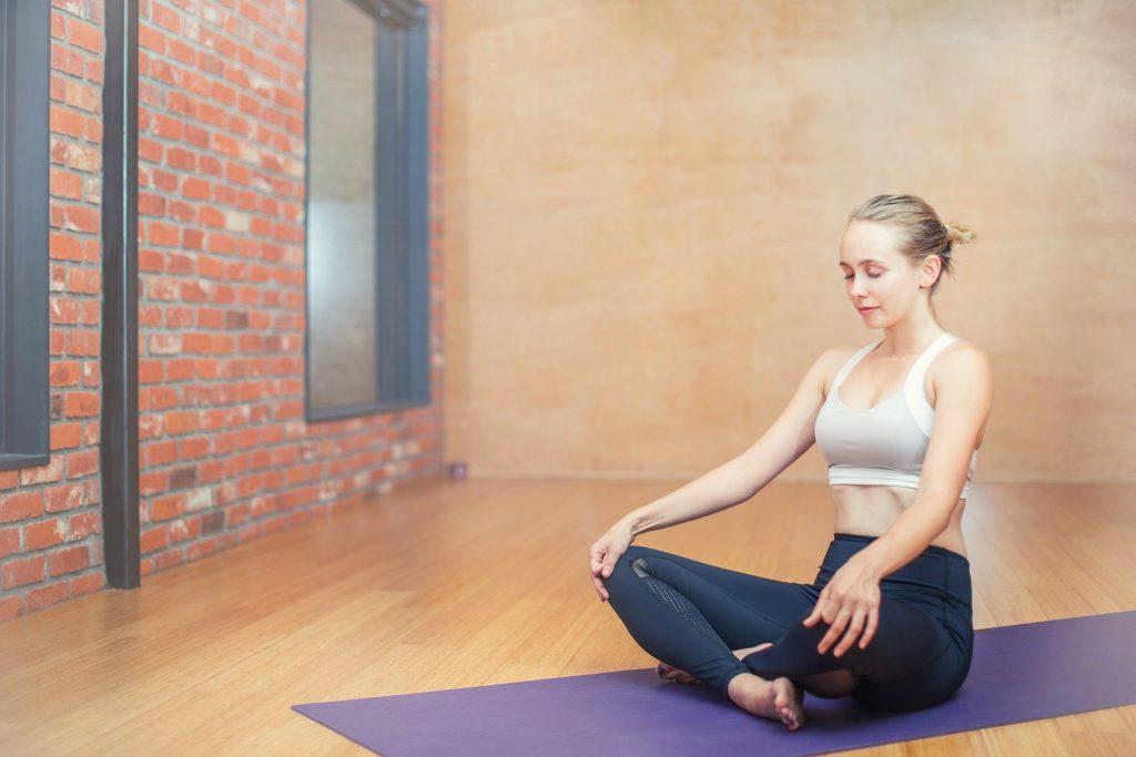 Frau im Schneidersitz auf Yoga-Matte mit geschlossenen Augen