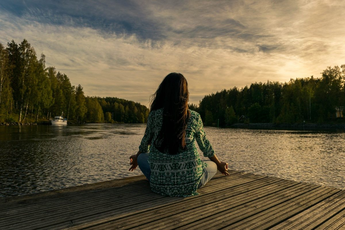 Frau sitzt draußen am Wasser und entspannt