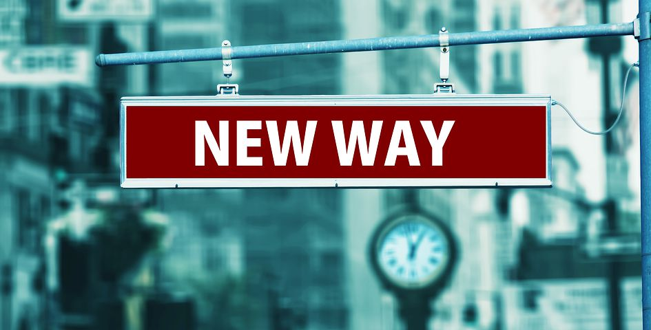 """Schild mit dem Text """"New Way"""", im Hintergrund eine Uhr auf der Straße"""